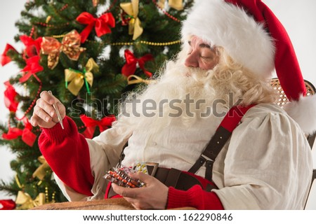 Astonished Santa Claus measuring his temperature with thermometer, feeling ill. Christmas in Danger!