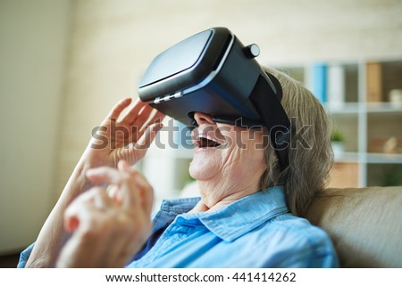 Astonished senior woman with vr glasses - stock photo