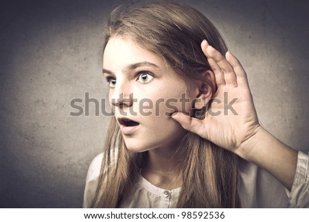 Astonished teenage girl lending an ear to some talk - stock photo
