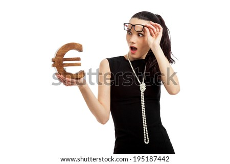 astonished woman wearing black dress holding euro sign over white background - stock photo