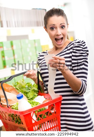 Astonished young woman with full shopping basket checking a grocery receipt. - stock photo