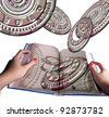 astrology book in hands and horoscope wheels - stock photo