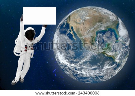 Astronaut holding blank banner for advertise floating in space and Earth background. Elements of this image furnished by NASA