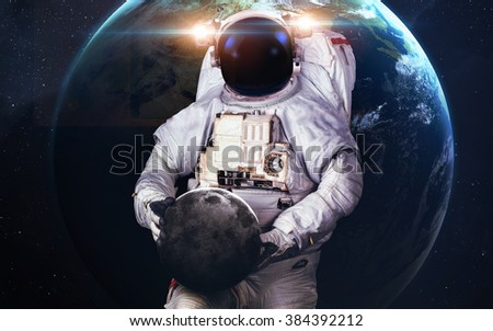Astronaut holding planet. Elements of this image furnished by NASA - stock photo
