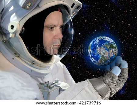 Astronaut looking small planet earth on the background of stars. Cosmonaut in space, watching a small planet in his hand. Globe in the universe. - stock photo