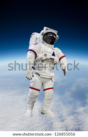 Astronaut Wearing Pressure Suit in a Space Background - stock photo