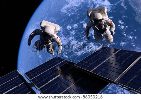 Astronauts in space around the solar battarei. - stock photo
