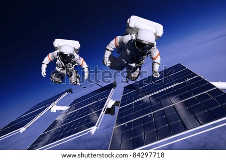 Astronauts in space around the solar panels - stock photo