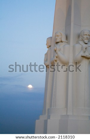 Astronomer's Monument at the Griffith Observatory with the moon.  Los Angeles landmark. - stock photo