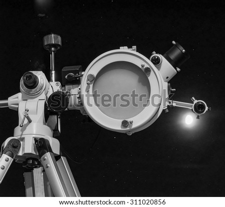 Astronomical telescope over dark sky with the moon - selective focus on telescope in black and white - stock photo
