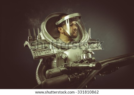 Astronomy, spaceman with plasma gun and helmet glass - stock photo