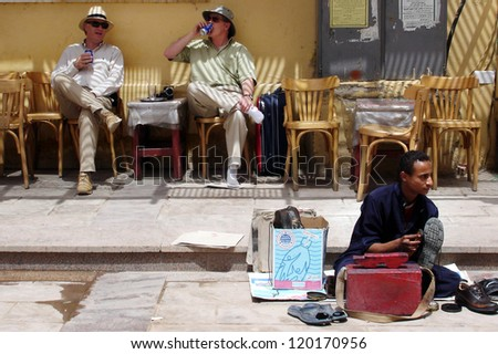 ASWAN - APRIL 28:Western visitor smoking pipe in a cafe in Aswan,Egypt on April 28 2007.The number of tourists visiting Egypt dropped by more than a third since the Egyptian revolution on Jan 25 2011. - stock photo