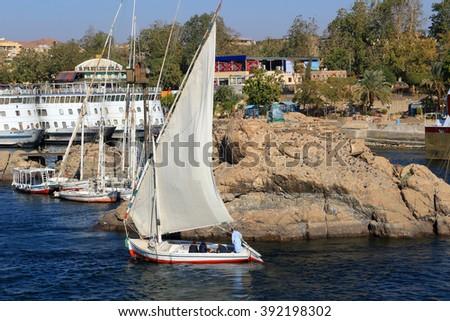 ASWAN, EGYPT - FEBRUARY 2, 2016: Boats docked and fellucas sailing along the shore of the Nile River at Aswan, Egypt - stock photo