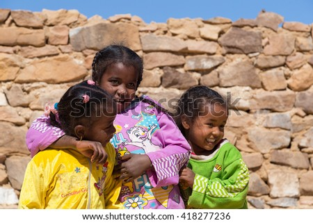 ASWAN, EGYPT - FEBRUARY 7, 2016: Local girls in Nubian village on the Nile posing for camera. - stock photo