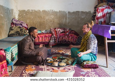 ASWAN, EGYPT - FEBRUARY 7, 2016: Local man and tourist having traditional Egyptian / Nubian lunch.