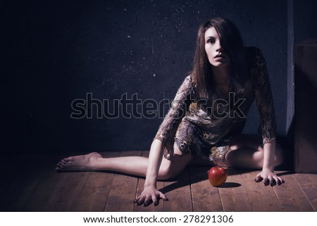 Asylum. Lonely mad woman with red apple sitting on a floor. Low key.
