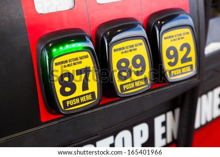 At a gas station multiple options are available for the type of gas to put in your vehicle and in this scenario the cheapest type of regular is selected since gas prices are rising and high. - stock photo