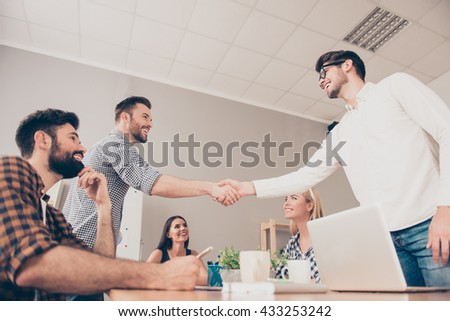 at a  meeting  young  businessmen shake hands to each other - stock photo
