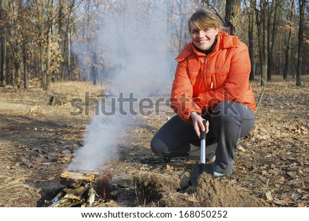At a picnic, in the autumn forest, bright sunny day girl kindles a fire and holding a shovel, fire smokes heavily - stock photo