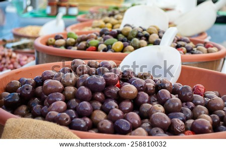 at a street market are selling green and black olives - stock photo