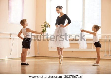 At ballet dancing class: young boy and girl giving flowers and veil to older student while she is dancing en pointe  - stock photo