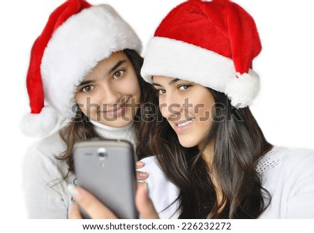 At Christmas Time.  Two beautiful girls taking self-portrait with mobile phone in Santa hats, isolated on white background.  - stock photo