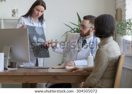 At doctor office. Doctor holding mri xray and talking to patient - stock photo