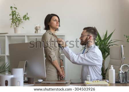 At doctor office. Doctor listening patient breathing - stock photo