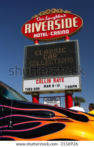 At Don Laughlin's Riverside Hotel and Casino in Laughlin, Nevada, is a marquee advertising a classic car collection museum there. In the foreground is a PT Cruiser. - stock photo