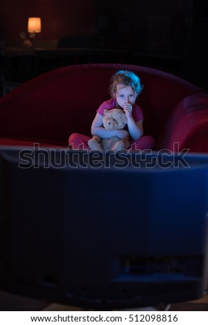 kids watching tv at night. at home by night, a lonely little girl sitting on couch, holding her kids watching tv night e