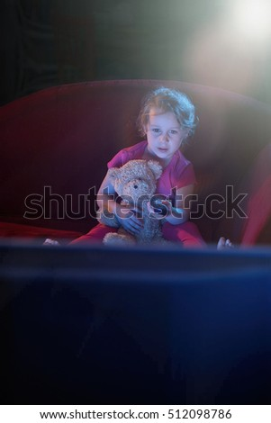 kids watching tv at night. at home by night. a lonely little girl sitting on red couch watching tv kids night