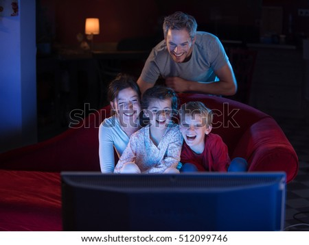 kids watching tv at night. at home by night, cheerful family sitting in a red couch and watching funny kids tv night s