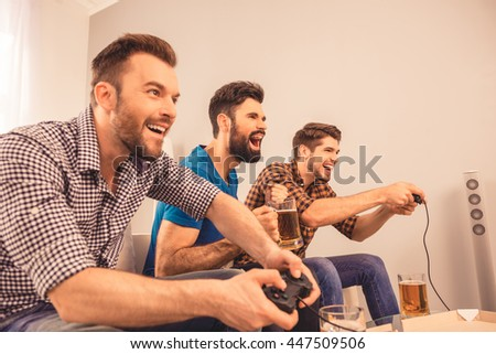 at home excited happy cheerful men play video game with joystick - stock photo