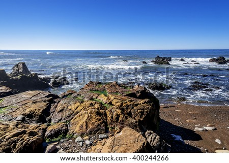 At sunrise, blue sky, rock and unusual geological formations at low tide, along the rugged Big Sur coastline, near Monterey, CA. on the California Central Coast. - stock photo