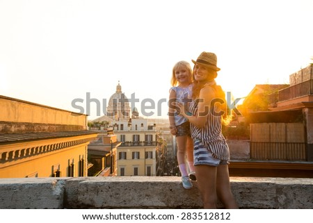 At sunset, a brunette mother in shorts and wearing a hat is holding her daughter who is standing on a ledge above the city of Rome. In the distance, St. Peter's Basilica. - stock photo