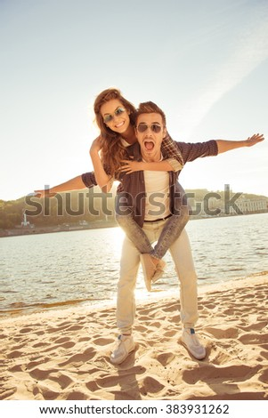 at sunset happy young man piggybacking his girlfriend at the seaside - stock photo
