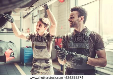 At the auto service. Handsome young auto mechanics in uniform are smiling while repairing car