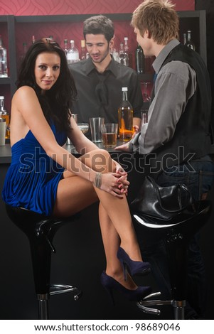 At the bar attractive young woman wear blue dress