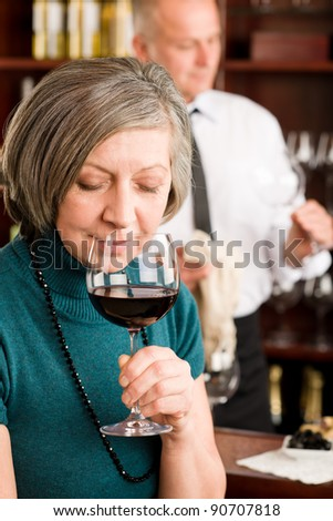 At the bar - happy senior woman taste red wine glass - stock photo