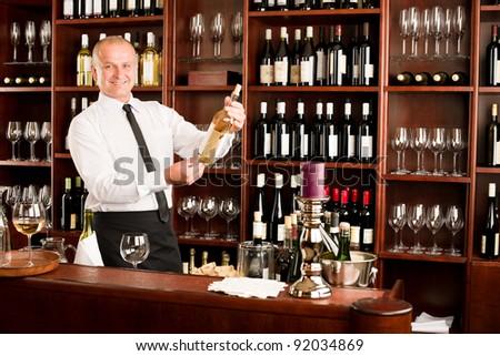 At the bar - waiter hold bottle white wine in restaurant - stock photo