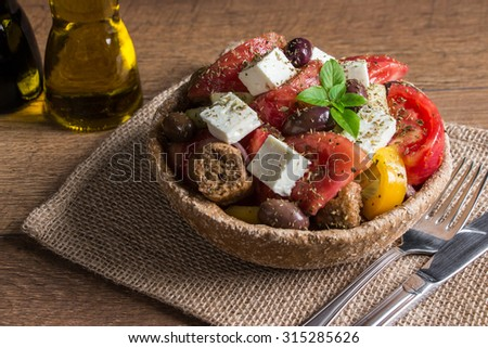 At the center of the frame bread bowl of Greek salad on a table-napkin of burlap in the background olive oil, balsamic vinegar.  Cretan Greek salad with croutons. Close-up. Horizontal shot. Daylight. - stock photo