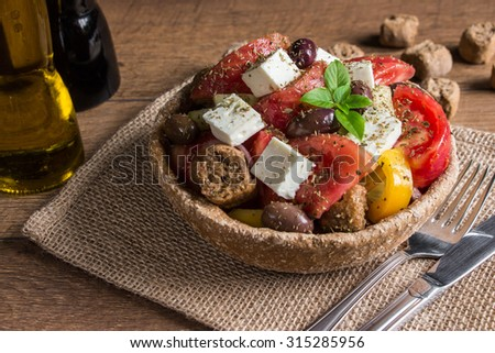 At the center of the frame bread bowl of Greek salad on a table-napkin of burlap in the background olive oil, balsamic vinegar, croutons.  Cretan Greek salad with croutons. Horizontal. Daylight.    - stock photo