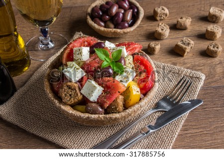 At the center the bread bowl of Greek salad on a table-napkin of burlap in the background olive oil, balsamic vinegar,  glass of wine, olives croutons.  Cretan Greek with croutons. Daylight.    - stock photo