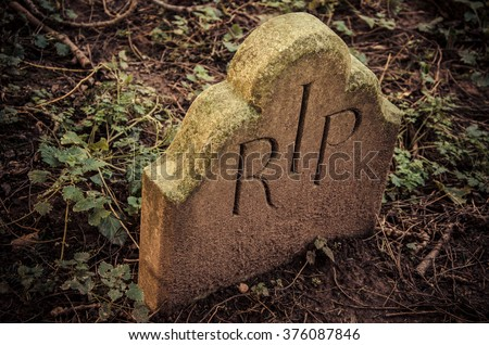 At the End - RIP engraved on tomb. Little tombstone with R.I.P inscription (Rest In Peace) in an old English graveyard. - stock photo