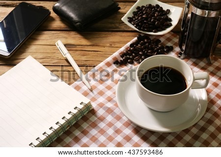 At the table with a cup of coffee,coffee bean, Notebook,smartphone, pen and notebook in warm tone,Take a break  - stock photo