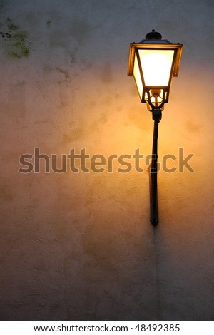 At the twilight an old street lamppost on an ancient wall - stock photo