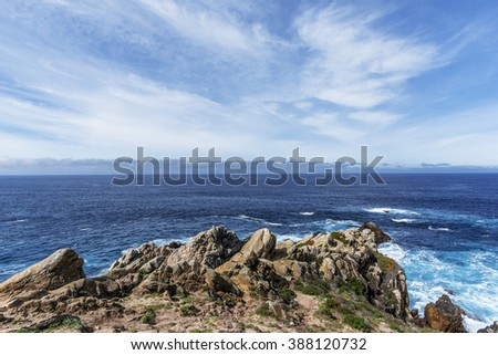 At the west side of Cypress Grove Trail you see a outcropping of unusual geological rock formations, blue seas, white clouds & blue sky along, an endless horizon, at Point Lobos State Natural Reserve. - stock photo