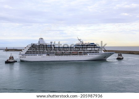 ATHENA GREECE - MAY 20 2014: A  smaller cruise liner  with the help of two tugboats arrives in  port of Athena. Athena offers countless historical sites  and rich history for tourists.    - stock photo