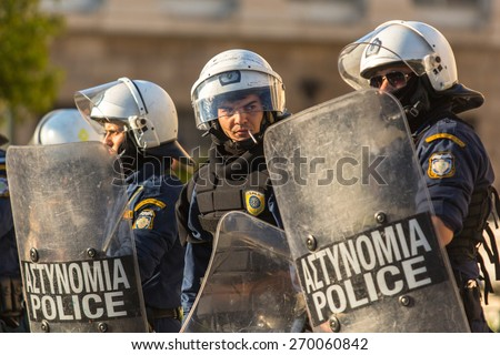 ATHENS, GREECE - APR 16, 2015: Riot police with their shield, take cover during a rally in front of the Athens University, which is under occupation by protesters leftist and anarchist groups. - stock photo