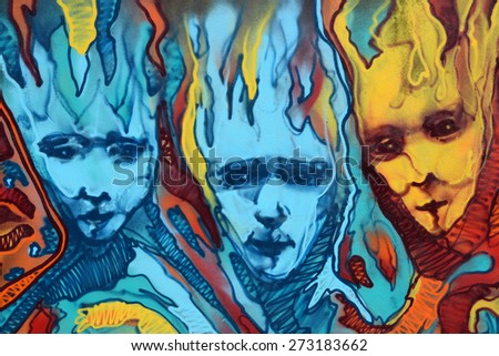 ATHENS, GREECE - APRIL 27, 2015: Abstract graffiti three distorted faces with flames. Colorful urban street art. - stock photo